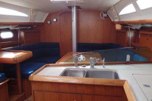L'intérieur de L'Inko, table à carte, cabine avant skipper, carré et cuisine
